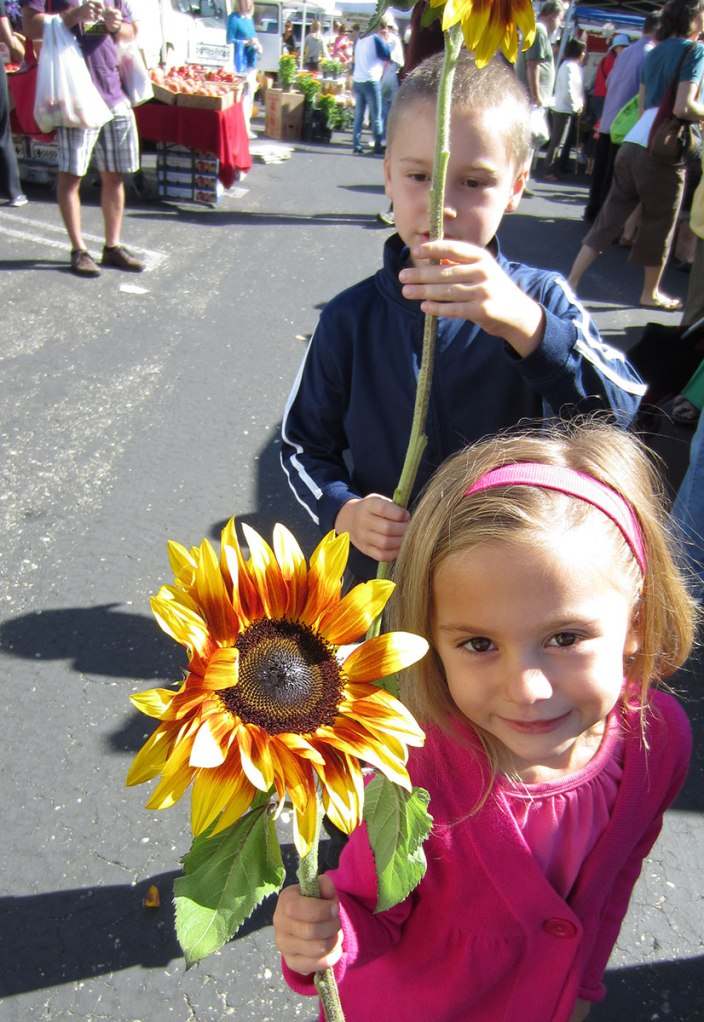 Iain and Liliana with sunflowers at the SLO Farmers Market