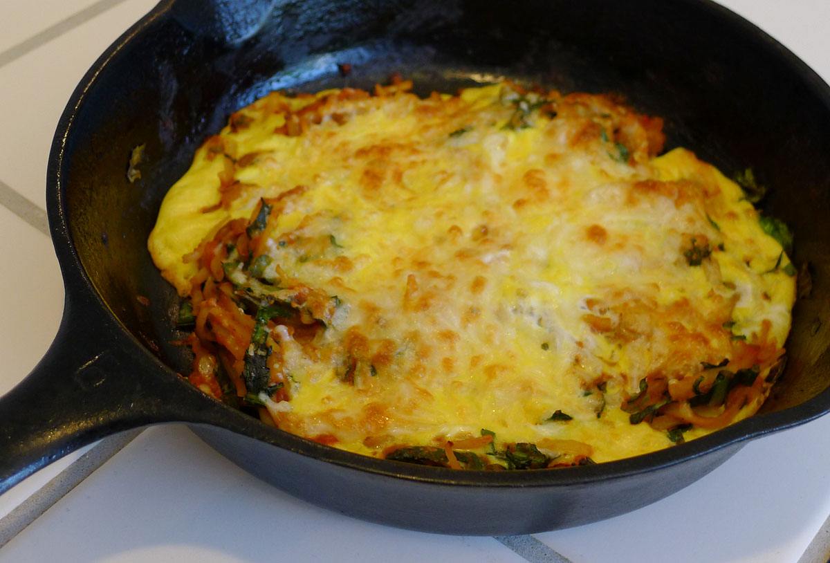 one egg frittata made with sauteed kale and leftover pasta