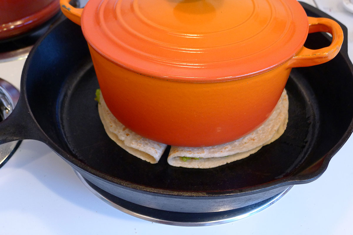 quesadillas weighted with a Le Creuset saucepan